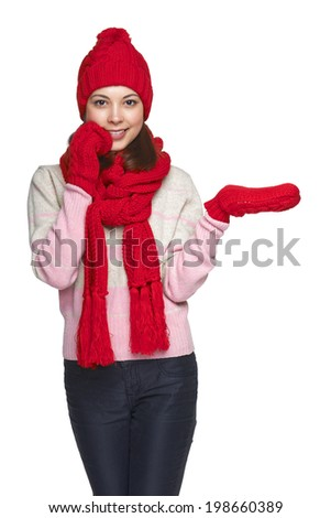 Beautiful woman in hat, muffler and mittens showing / holding on the palm blank copy space, over white background - stock photo