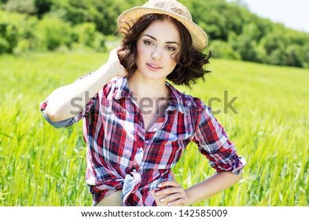 Beautiful  woman in hat on summer meadow - stock photo