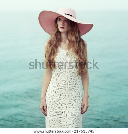 Beautiful woman in hat on the sea. Fashion photo - stock photo