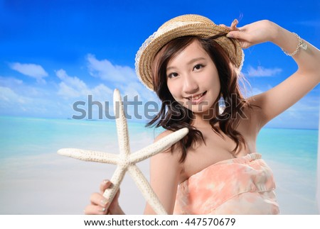 Beautiful woman in hat with starfish poses on beach - stock photo