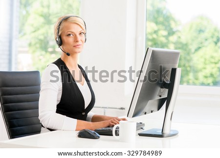 Beautiful woman in headset working in call center. - stock photo