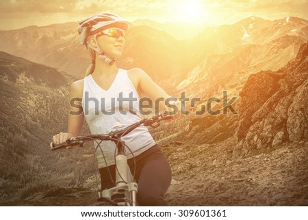 Beautiful woman in helmet and glasses stay on the bicycle around mountains.