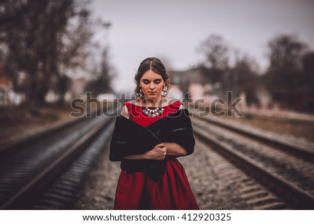 Beautiful Woman in Historical Garment Standing on the Abandoned Railway Station. Book Cover Concept. - stock photo
