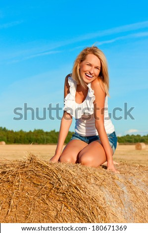 Beautiful woman in jeans short and white shirt posing on a wheat bale in a field - stock photo