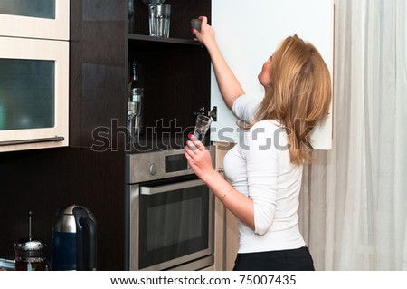 Beautiful woman in kitchen interior. One person only - stock photo