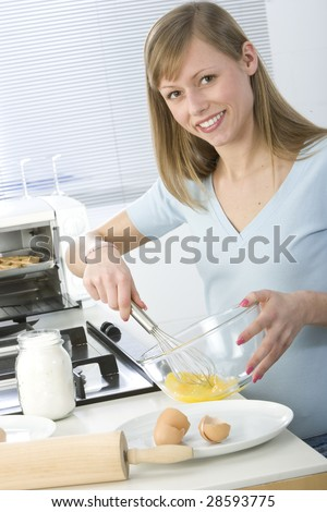 Beautiful woman in kitchen is making a cake - stock photo