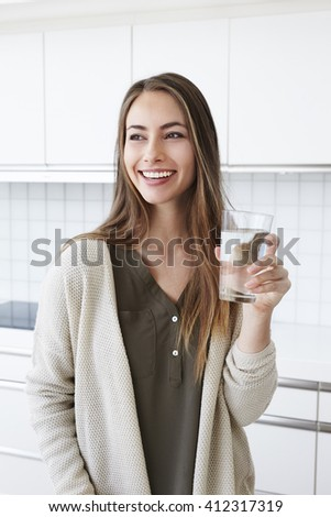 Beautiful woman in kitchen with water