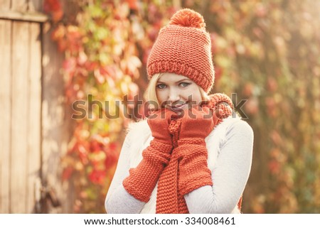 beautiful woman in knitted outfit smiling against autumn foliage - stock photo