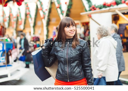 beautiful woman in leather jacket with shopping bags on christmas market