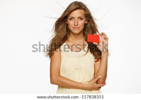 Beautiful woman in light dress holding empty credit card isolated on white background - stock photo