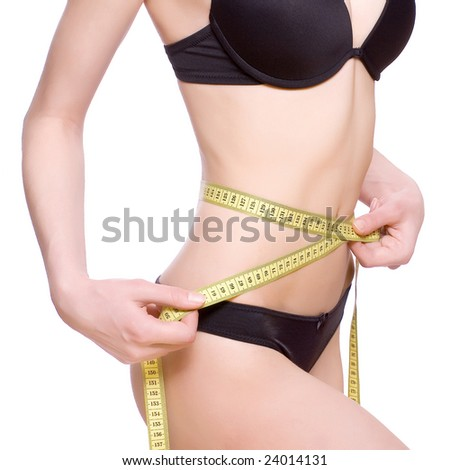 beautiful woman in lingerie measuring her waist - stock photo