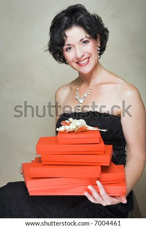 Beautiful woman in little black dress of lace, wearing pearls, sitting with red boxes piled on her lap, short curly hair