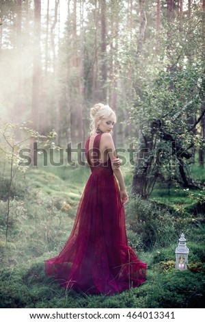 Beautiful woman in long red dress in the woods, mysterious portrait, artistic intent