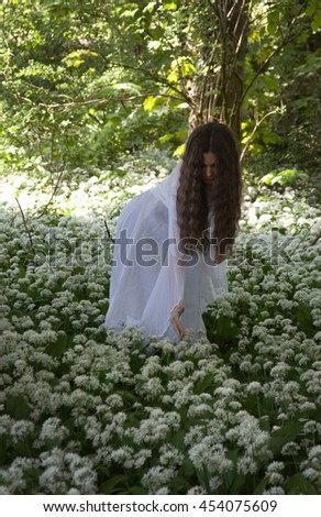 Beautiful woman in long white dress picking flowers in a forest