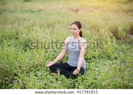 Beautiful woman in lotus position practicing yoga.