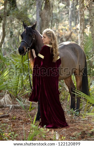 beautiful woman in medieval dress and arabian horse in forest - stock photo