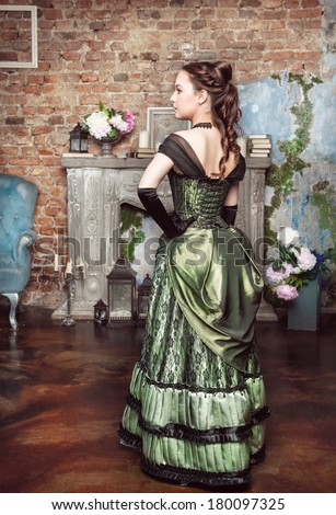 Beautiful woman in medieval dress near fireplace - stock photo