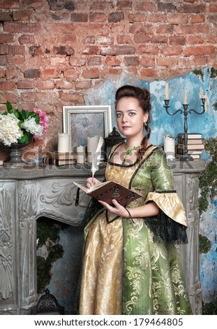 Beautiful woman in medieval dress with book and feather