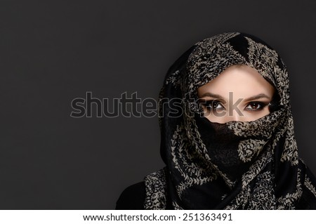 Beautiful Woman in Middle Eastern Niqab veil on grey background - stock photo