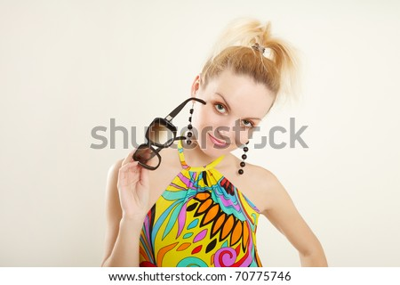 Beautiful woman in multicolor dress and with glasses on white background