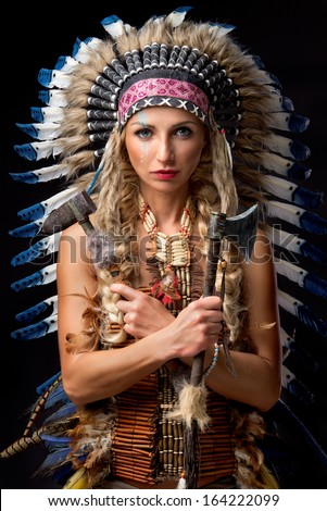 Beautiful woman in native american costume with feathers - stock photo