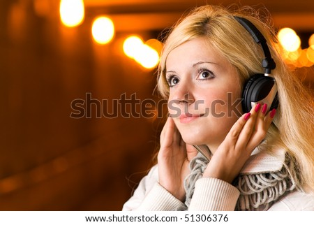 Beautiful woman in night tunnel listens to music through headphones.