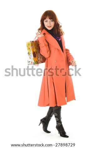 Beautiful woman in orange coat with bags. Isolated on white background