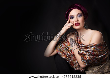 beautiful woman in oriental style with mehendi in hijab on black background. Copy space. - stock photo