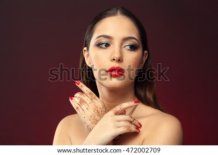beautiful woman in oriental style with mehendi on dark background