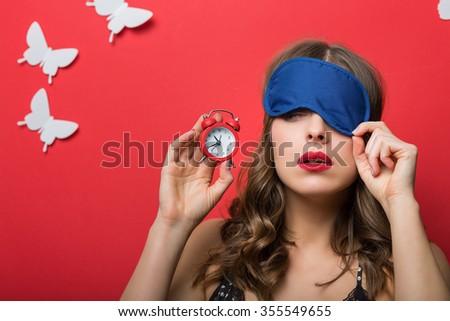 Beautiful woman in pajamas cami top and alarm clock - stock photo
