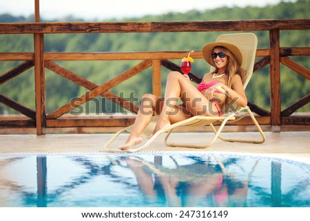 Beautiful woman in pink bikini on lounge chair enjoying by the pool. She has a hat on her head and holding a glass of cocktail - stock photo