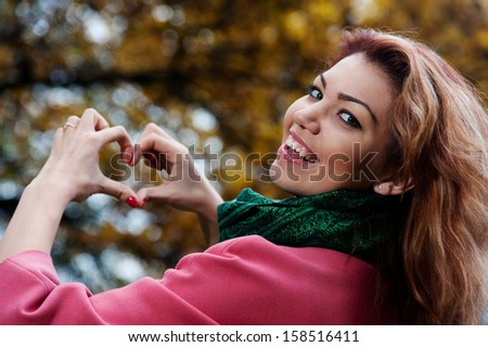 Beautiful woman in pink coat showing heart in the Park, autumn background