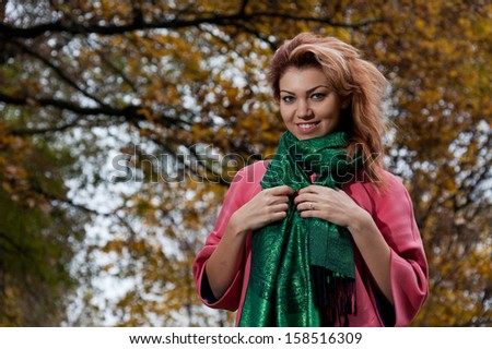 Beautiful woman in pink coat walks in the Park, autumn background