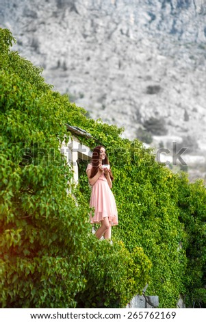Beautiful woman in pink dress standing with coffee cup on the balcony of green house in the mountains - stock photo