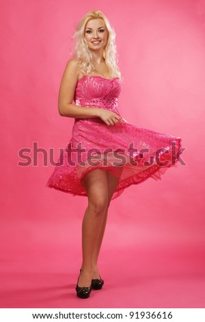 Beautiful woman in pink dress, studio portrait - stock photo