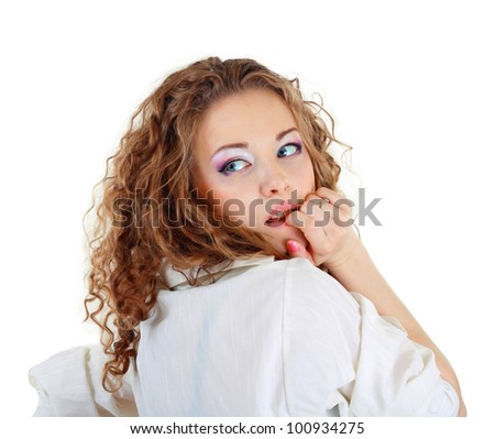 Beautiful woman in pink shirt and black shoese sitting on the bed white background - stock photo