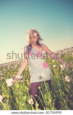 Beautiful woman in poppy flowers. Vintage colors - stock photo