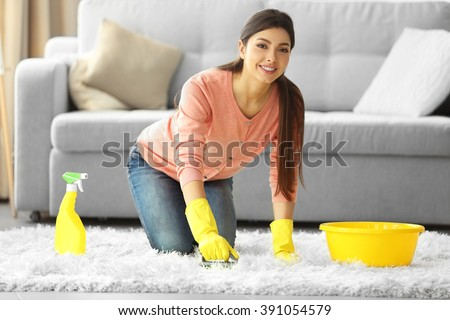 Beautiful woman in protective gloves cleaning carpet with brush and spray - stock photo