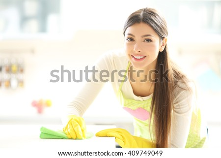 Beautiful woman in protective gloves cleaning kitchen table with rag - stock photo