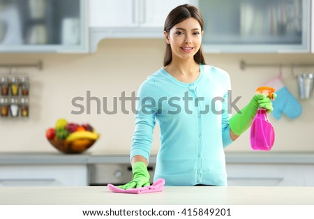 Beautiful woman in protective gloves cleaning kitchen table with rag and spray - stock photo