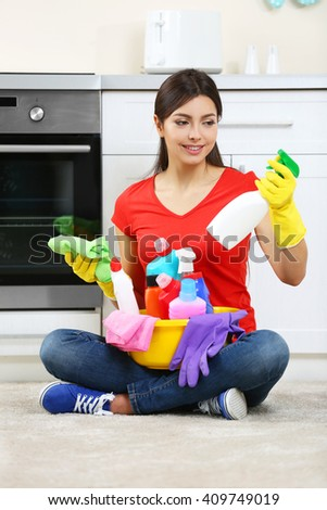 Beautiful woman in protective gloves with different cleaning sprays - stock photo