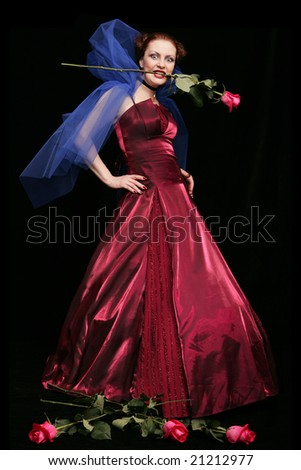 Beautiful woman in purple dress with rose in her mouth
