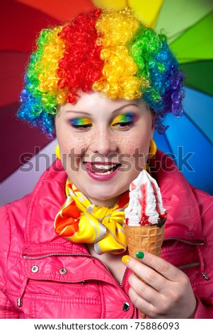 Beautiful woman in rainbow clown wig with freckles and creative rainbow make-up holding strawberry ice cream and smacks her lips at rainbow background - stock photo