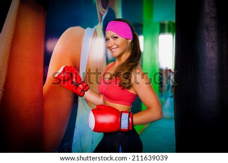beautiful woman in red boxing gloves next to pear