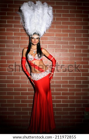 beautiful woman in red carnival costume with large fluffy white feathers - stock photo