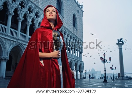Beautiful woman in red cloak against Dodge's Palace - stock photo
