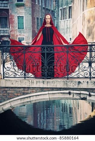 Beautiful woman in red cloak on a bridge. - stock photo