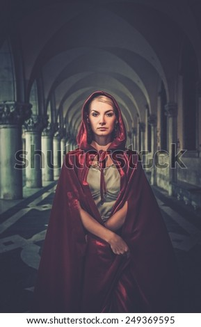 Beautiful woman in red cloak outdoor - stock photo