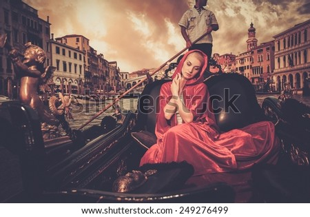Beautiful woman in red cloak riding on gondola - stock photo