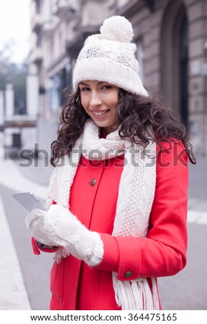 Beautiful Woman in Red Coat and and wool cap and glowes read messages on smartphone and smiling. Urban Space. Cold Weather